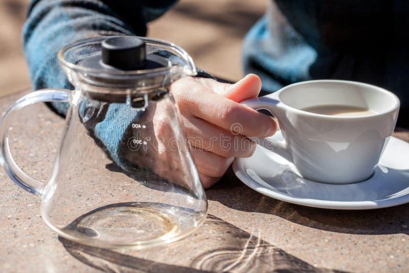 La main caucasienne de femme tient la tasse en céramique avec le thé noir et le lait, théière en verre vide à côté de elle images stock