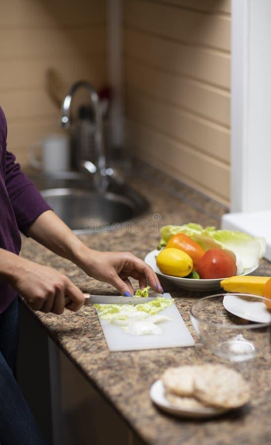 La main coupe des légumes pour la salade dans la cuisine photographie stock libre de droits