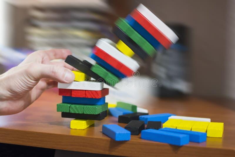 La main démantèle la tour des barres en bois multicolores image stock