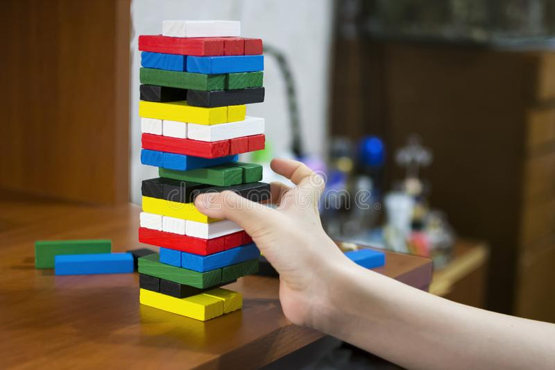 La main démantèle la tour des barres en bois multicolores photos stock
