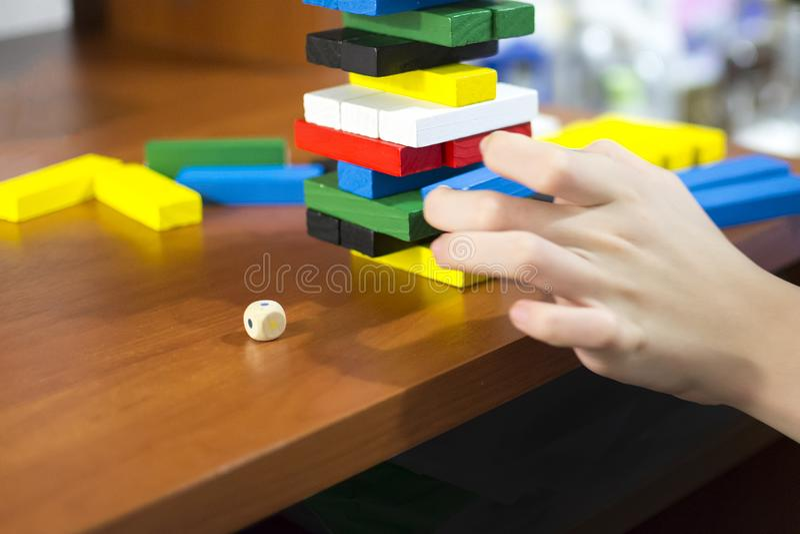 La main démantèle la tour des barres en bois multicolores image libre de droits
