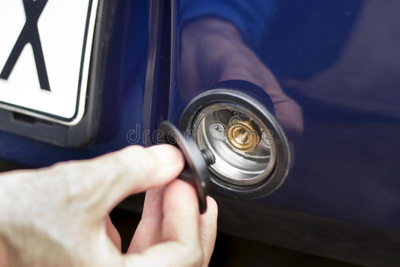 La main dévisse la prise de gaz de LPG dans le pare-chocs de la voiture images libres de droits