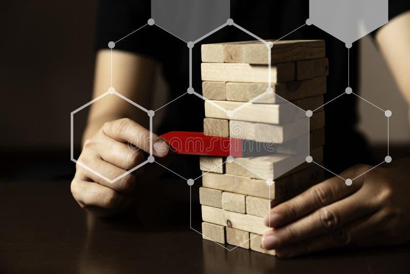La main d'affaires essayent de choisir le bloc en bois de couleur rouge images libres de droits