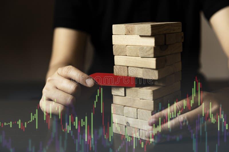 La main d'affaires essayent de choisir le bloc en bois de couleur rouge d'autres sur la table en bois et le démarrage noir d'asso photos libres de droits