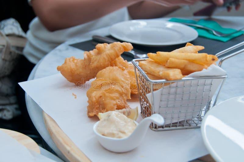 La main d'or croustillante a coupé des puces cuites à la friteuse avec des poissons de croustillant et les puces ont servi avec d images stock
