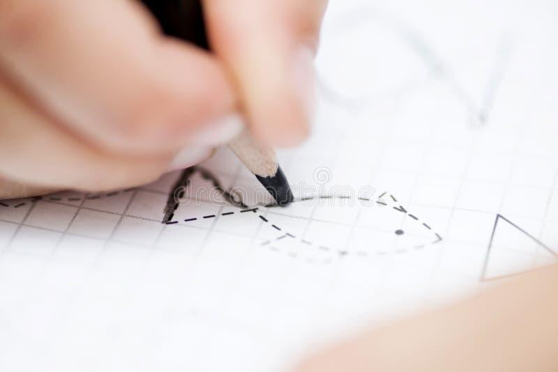 La main d'enfant dessine avec un crayon noir sur le papier photographie stock