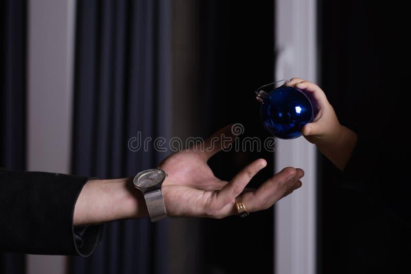 La main d'enfant passe la boule de Noël dans la paume du père Le concept de la préparation commune pour le papa et l'enfant de No image libre de droits