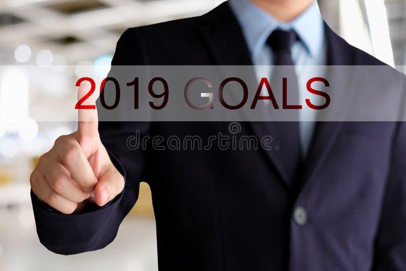 La main d'homme d'affaires touchant 2019 buts se boutonnent au-dessus du CCB de bureau de tache floue images libres de droits
