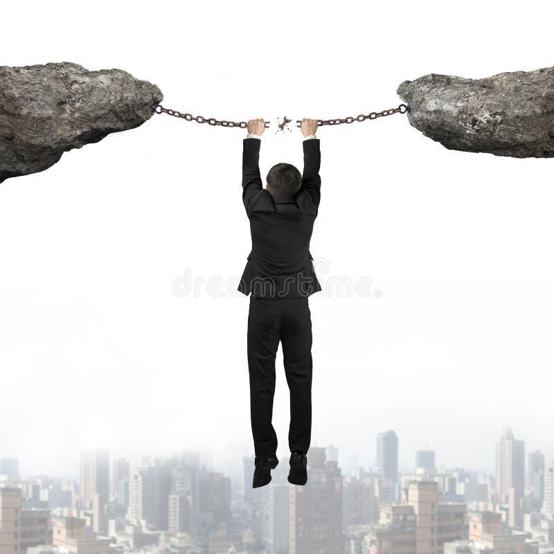 La main d'homme d'affaires accrochant les chaînes rouillées cassées de fer relient le Cl deux image libre de droits