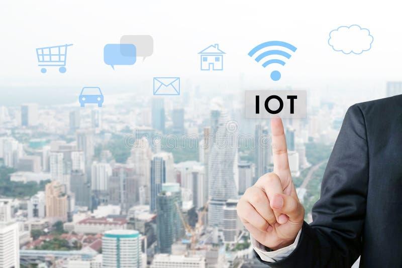 La main d'homme d'affaires dirigeant l'Internet des choses se boutonnent au-dessus de l'ico image stock