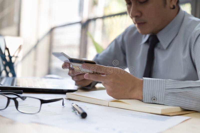 La main d'homme d'affaires jugeant une carte de crédit attentive a fait un p en ligne image libre de droits