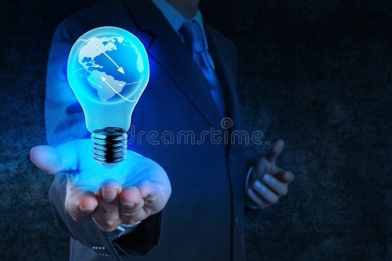 La main d'homme d'affaires montre l'ampoule avec le netwo de social de la terre de planète photo stock