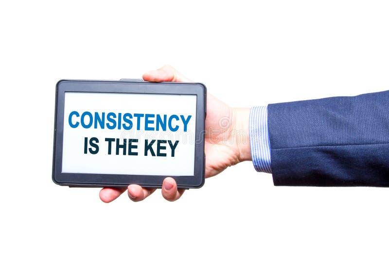 La main d'homme d'affaires tenant le comprimé avec la cohérence est le texte principal photos stock
