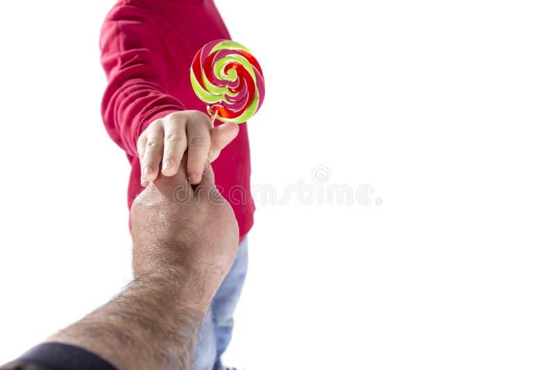 La main d'homme donnent la sucrerie à l'enfant images stock