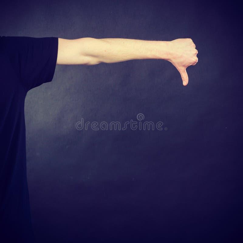 La main d'homme faisant le pouce font des gestes vers le bas image libre de droits