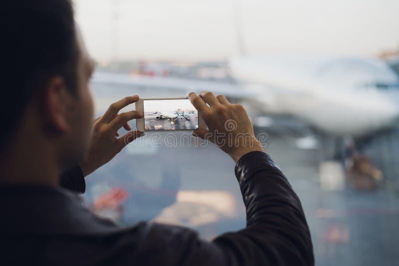 La main d'homme prennent la photo de l'avion utilisant le téléphone portable Photo de concept de tourisme photographie stock libre de droits