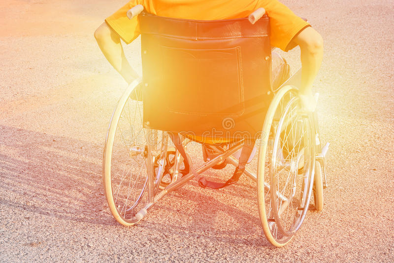 La main d'homme sur la roue du fauteuil roulant à la route en parc de ville nous emploient ton chaud d'incapacité d'assurance d'i photos stock