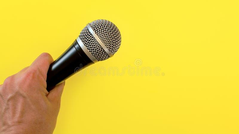 La main d'homme tient le microphone noir et argenté au-dessus du fond jaune photographie stock