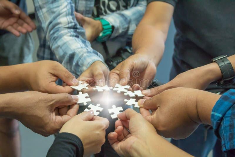 La main d'un groupe d'affaires qui veut mettre un morceau de puzzle photos stock