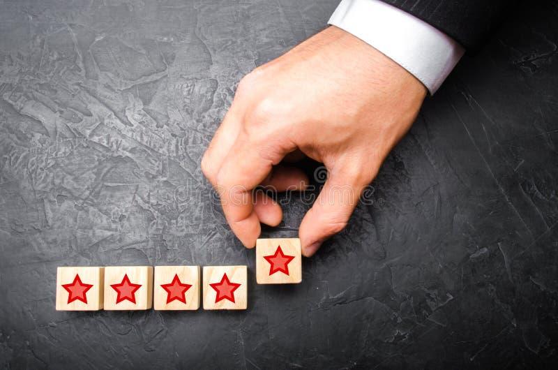 La main d'un homme d'affaires ajoute une cinquième étoile Le concept d'attribuer une nouvelle étoile et de soulever le statut, pr images stock