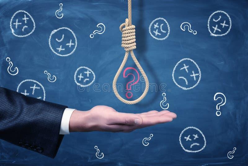 La main d'un homme d'affaires avec le noeud coulant d'un bourreau au-dessus de lui avec un point d'interrogation rouge de craie à image libre de droits