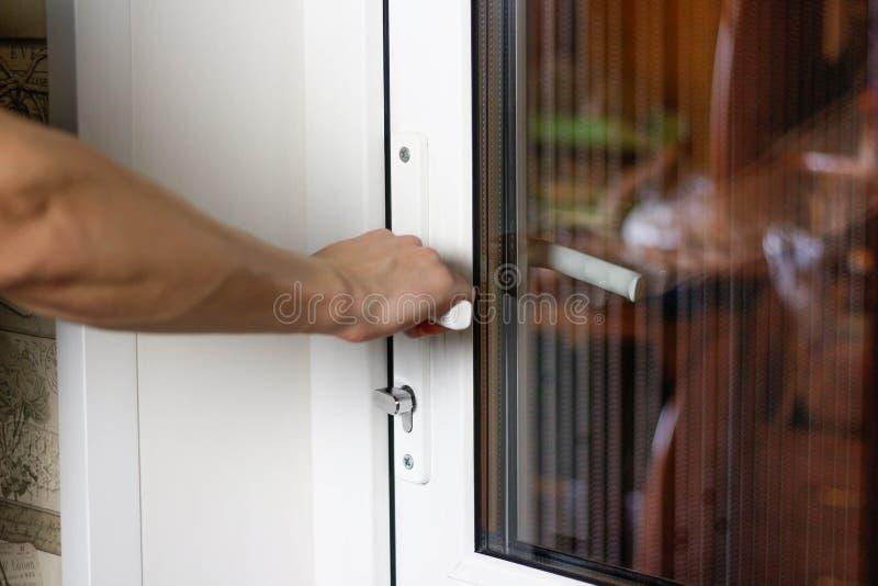 La main d'un homme ouvre une porte en plastique blanche Fin vers le haut images libres de droits