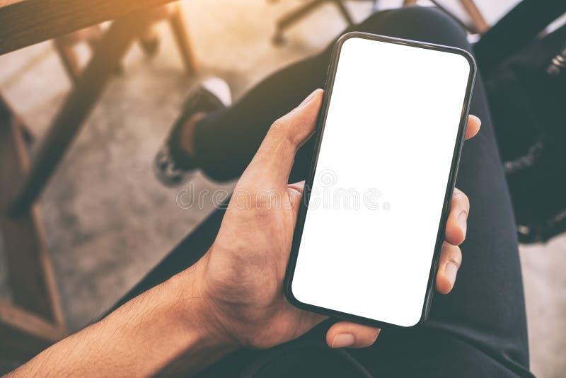 La main d'un homme tenant et à l'aide du téléphone portable noir avec l'écran blanc vide tout en se reposant en café image libre de droits