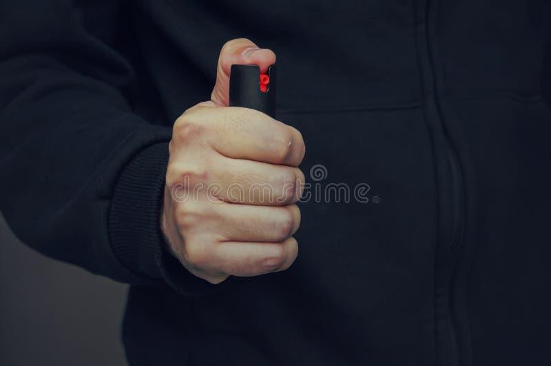 La main d'un homme tenant une petite bouteille de spray au poivre photos libres de droits