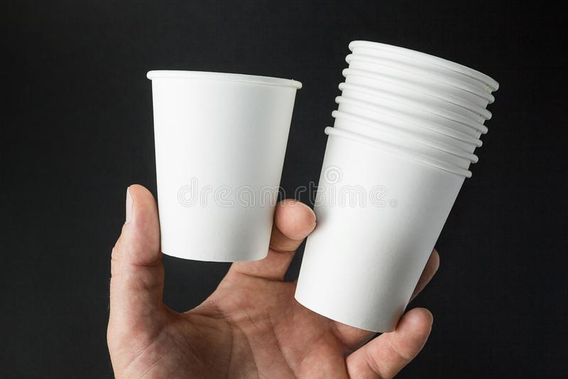 La main d'un homme tient des maquettes des tasses pour le café, le thé, la soude et le jus sur un fond noir images stock