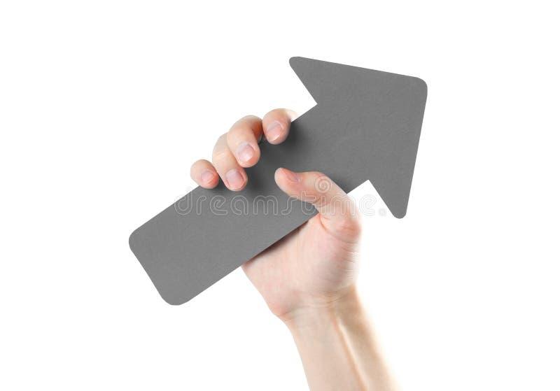 La main d'un homme tient une grande flèche grise Fin vers le haut D'isolement sur W photographie stock libre de droits