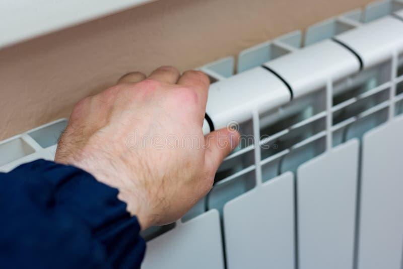 La main d'un homme vérifie la chaleur de la batterie de chauffage dans un appartement ou un bureau Préparation pour la saison fro photos libres de droits