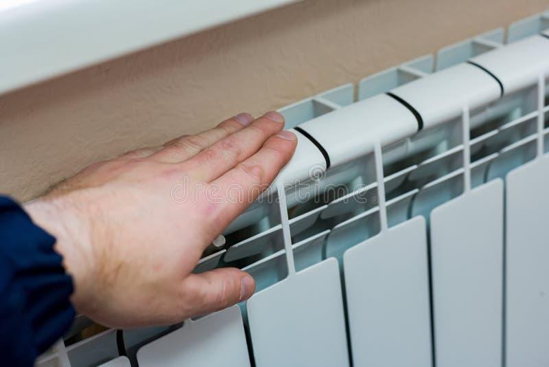 La main d'un homme vérifie la chaleur de la batterie de chauffage dans un appartement ou un bureau Préparation pour la saison fro image libre de droits