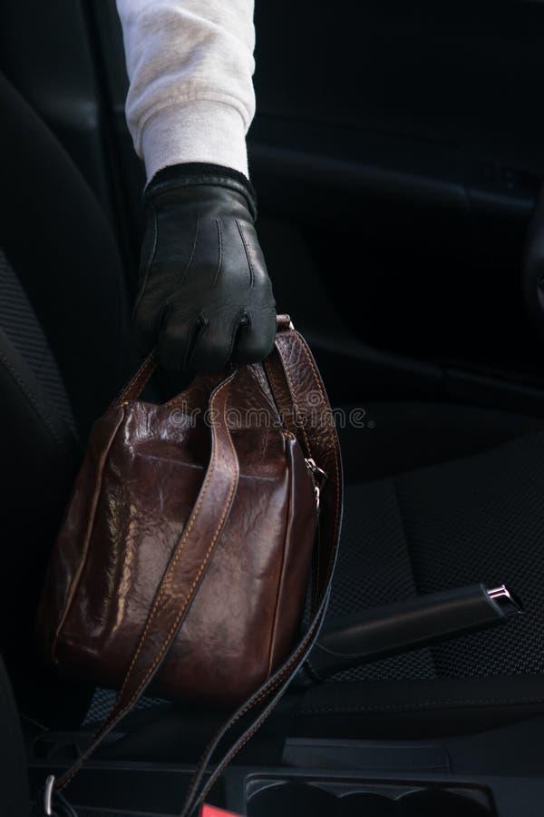 La main d'un voleur vole un sac des documents de la voiture, plan rapproché photo libre de droits