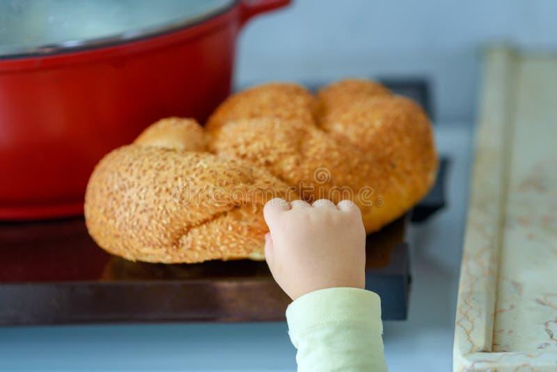 La main d'une prise affamée d'enfant et casser un morceau de pain photo libre de droits