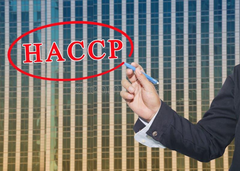 la main d'une utilisation d'homme d'affaires un stylo écrivent le système HACCP des textes photo stock