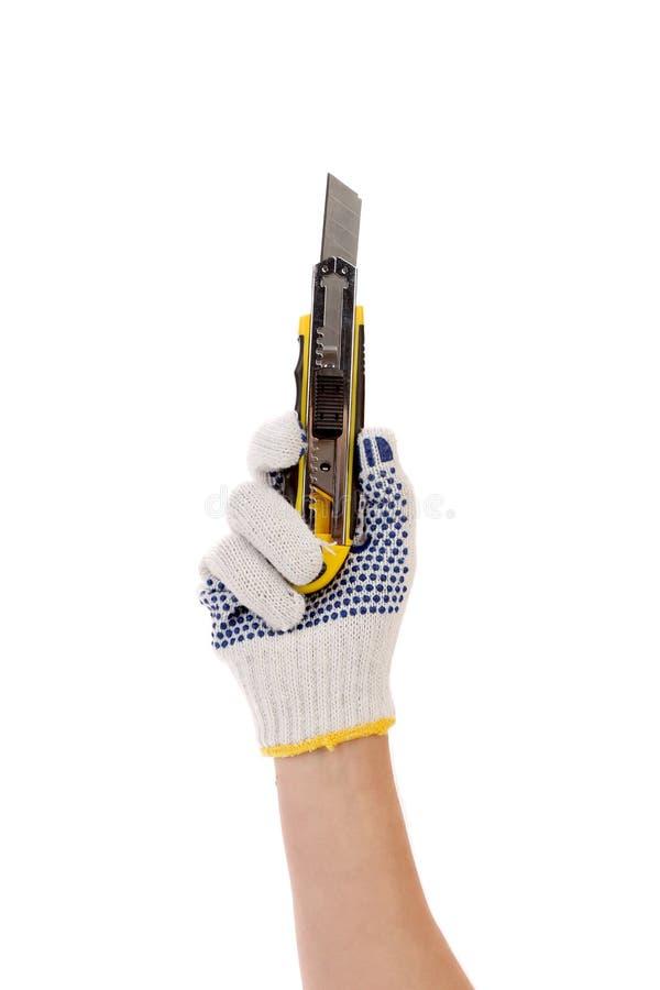 La main dans les gants tient le couteau de bureau. photos stock