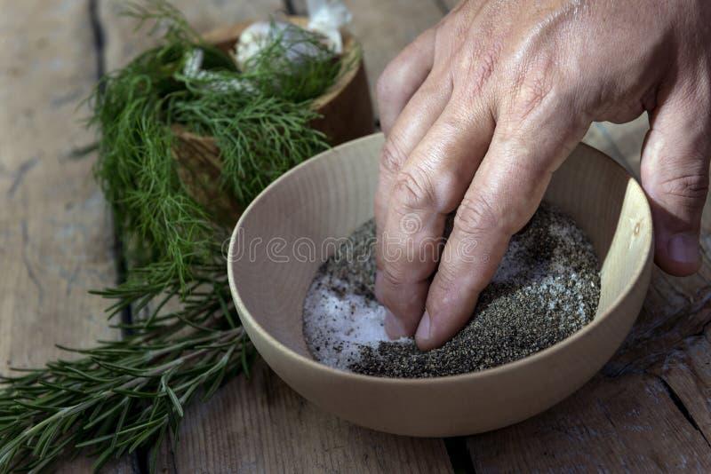 La main dans une cuvette en bois mélange le sel et le poivre images stock
