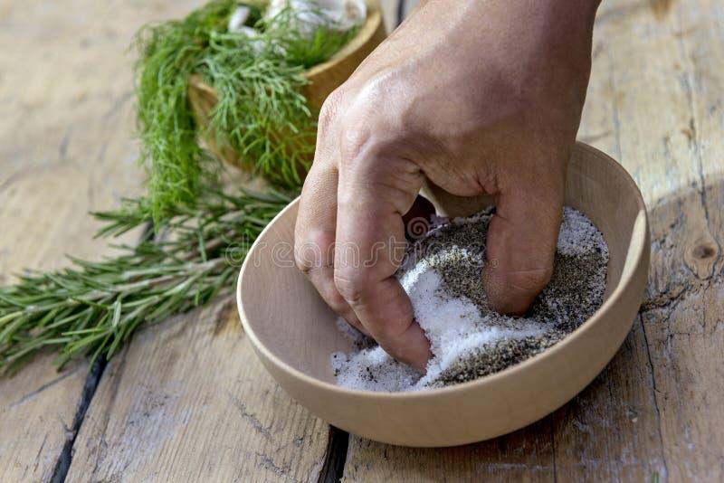 La main dans une cuvette en bois mélange le sel et le poivre image stock