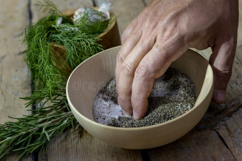La main dans une cuvette en bois mélange le sel et le poivre image libre de droits