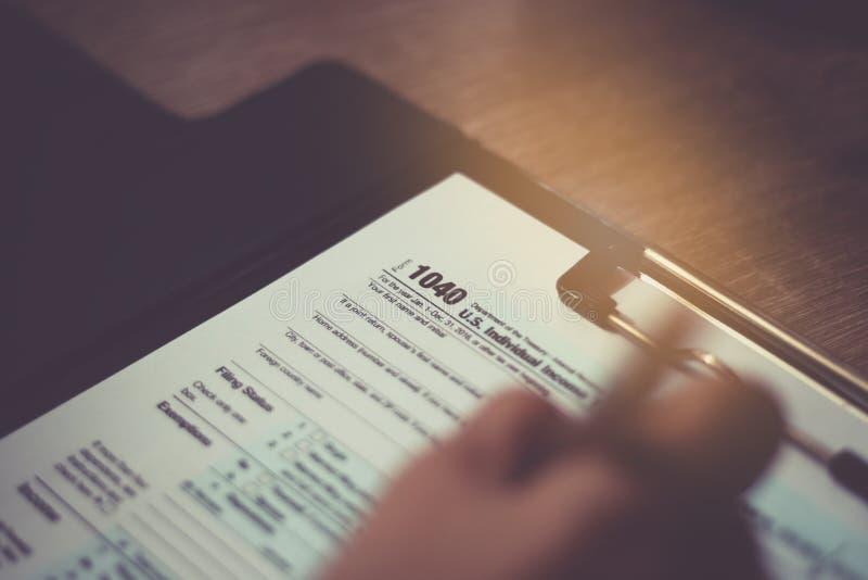 La main de femme écrivent sur la feuille d'impôt des USA 1040 au sujet du foyer sélectif photographie stock libre de droits
