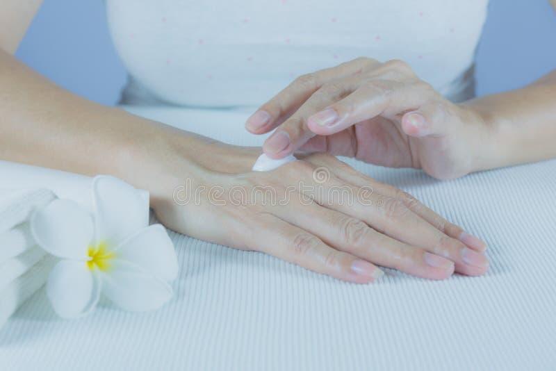 La main de la femme appliquent la lotion sur la peau de la main arrière images stock