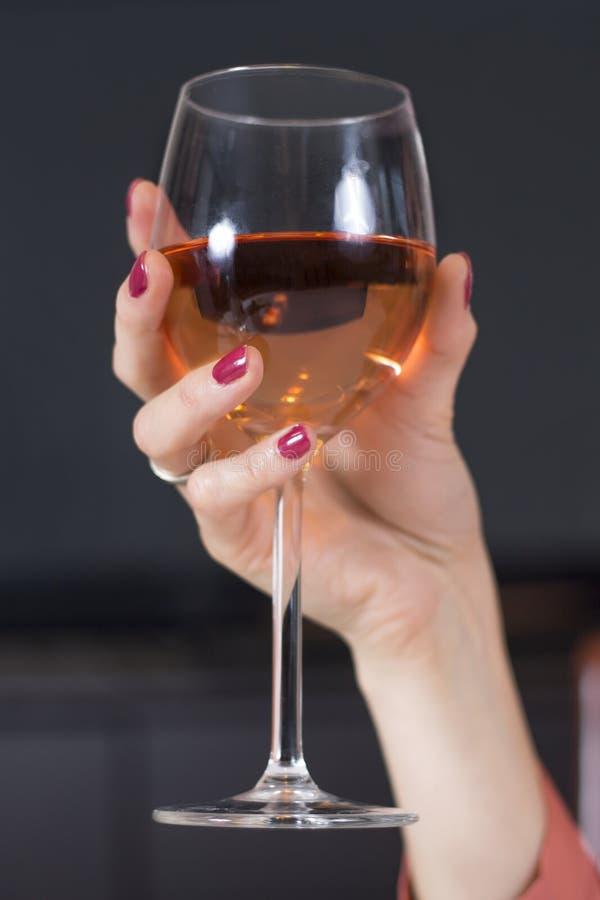La main de la femme avec des ongles rouges et un anneau l'épousant sur son doigt tient un verre de vin photos libres de droits