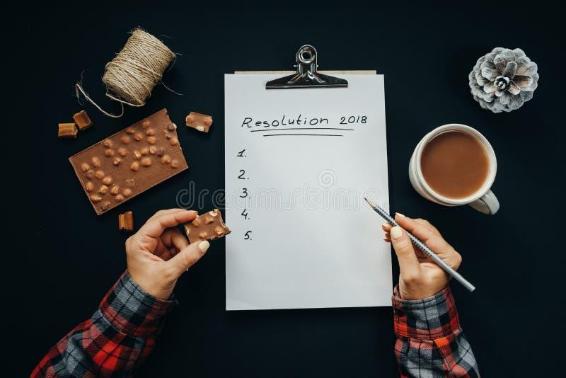 La main de la femme avec le crayon et le papier vide d'album avec la nouvelle année Reso photographie stock libre de droits
