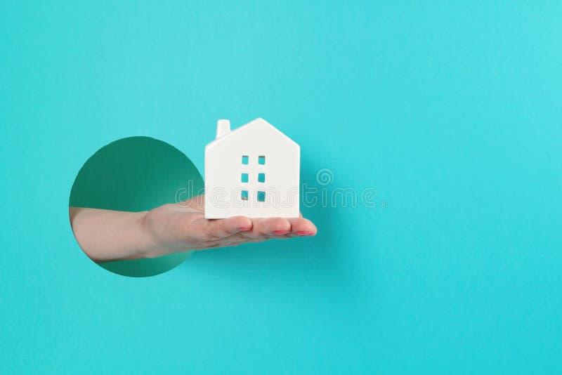 La main de la femme dans le trou de papier tenant une petite maison de jouets images libres de droits