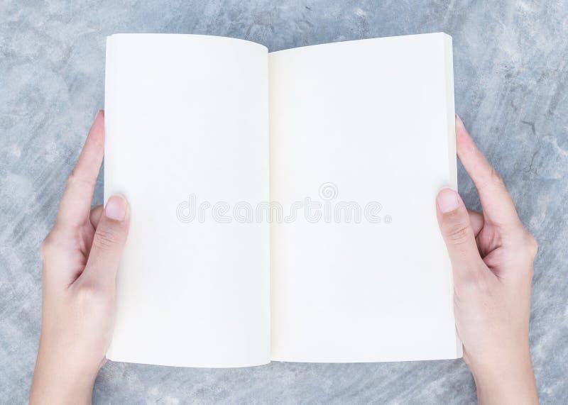 La main de femme de plan rapproché a indiqué un livre dans son temps gratuit sur le bureau concret à l'arrière-plan texturisé de  photos libres de droits