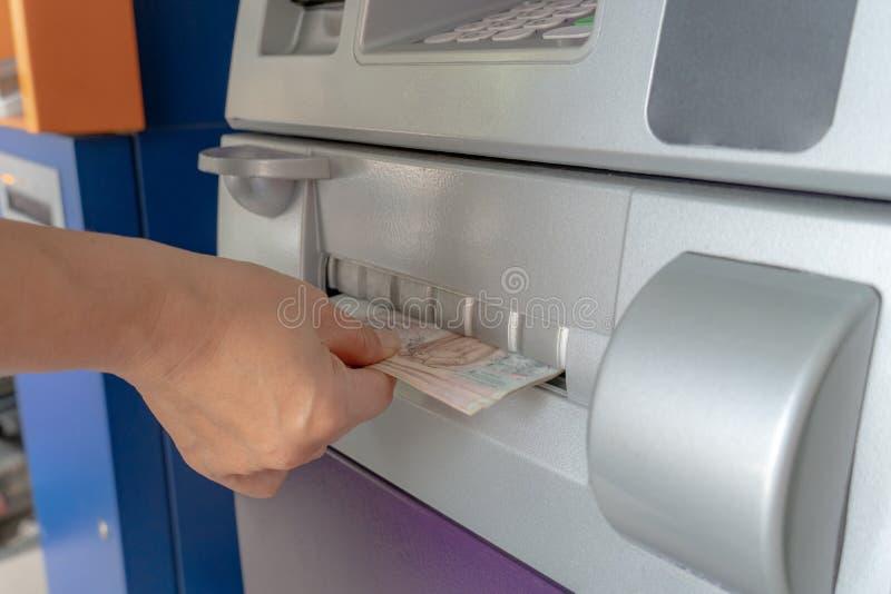 La main de la femme jugeant l'argent liquide retiré de l'atmosphère photo libre de droits