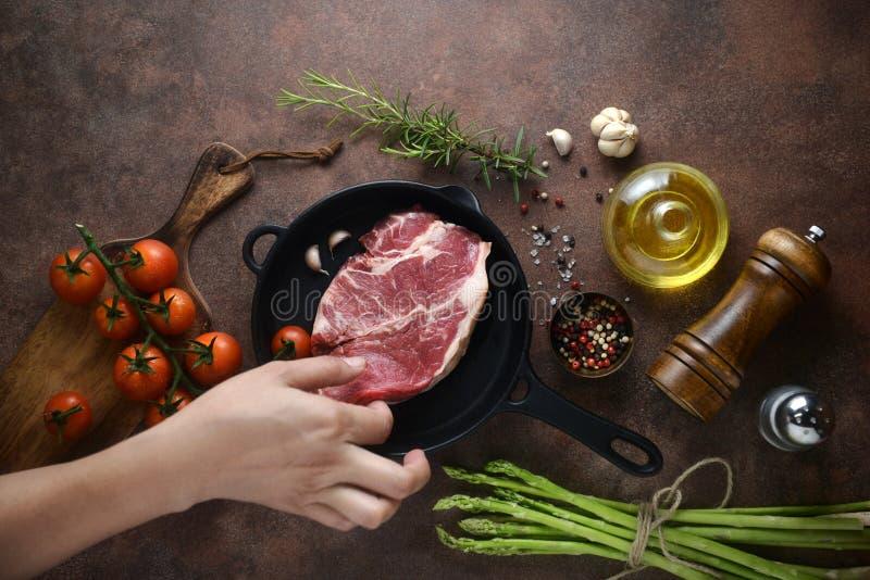 La main de femme a mis la viande dessus pour repasser la casserole pour que la préparation marine sur le fond d'ingrédients vue s images stock