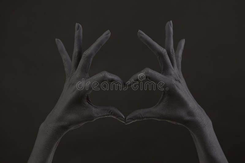 La main de la femme peinte noire faisant le symbole de coeur Symbole de l'amour, déclaration de l'amour image libre de droits