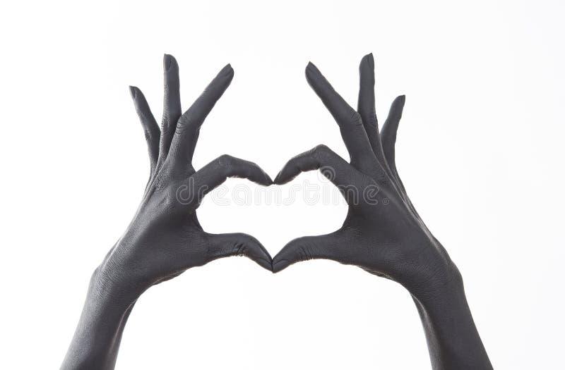 La main de la femme peinte noire faisant le symbole de coeur Symbole de l'amour, déclaration de l'amour Femme faisant la forme de image stock