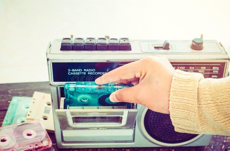 La main de femme tenant la cassette de bande avec le lecteur de cassettes et l'enregistreur pour écoutent musique images libres de droits